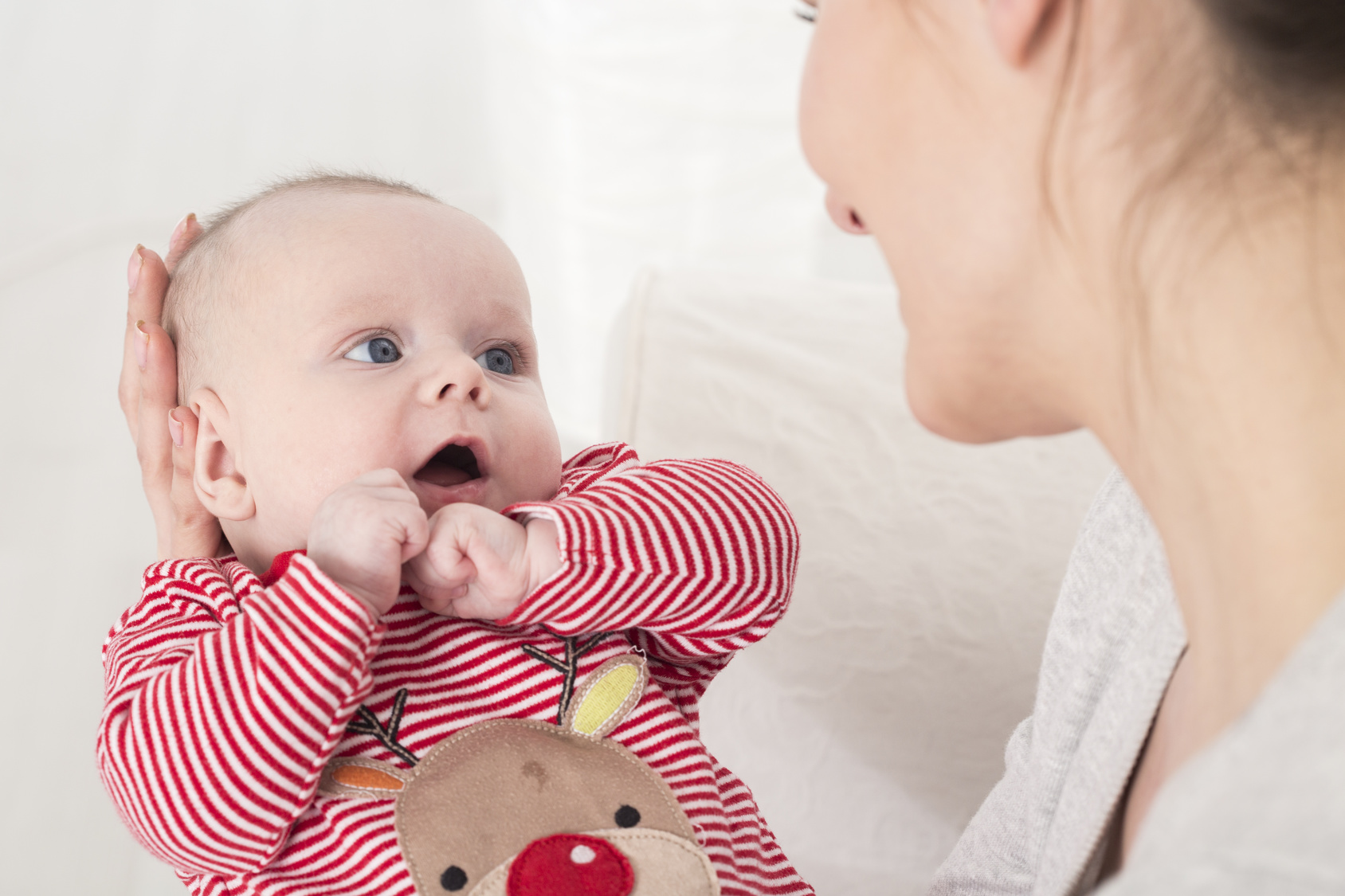 Smiling young mother holding the  little baby on hands. Baby wearing sleepers in stripes and reindeer