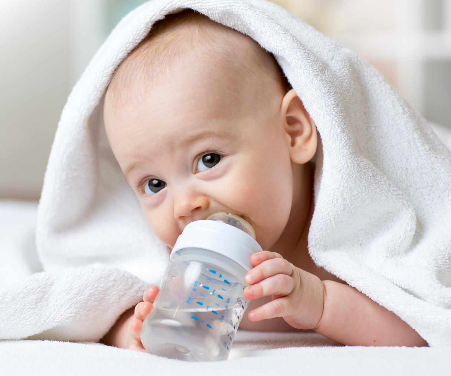 Happy baby drinks water from bottle wrapped towel after bathing