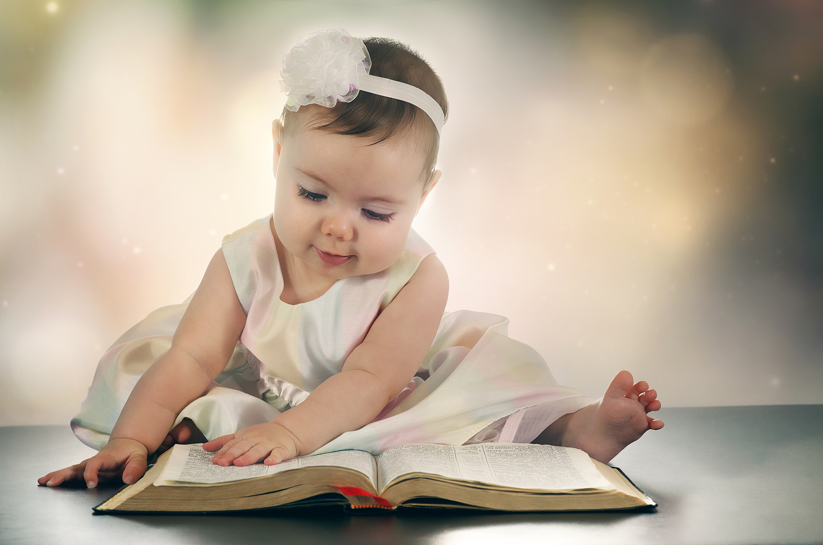 A young baby girl reads a Bible.